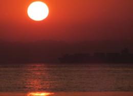 черное море на восходе, контейнеровоз на рейде в лучах заката.