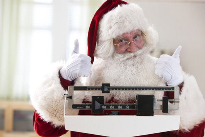 Santa Claus weighing himself with thumbs up